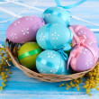 Easter eggs in basket and mimosa flowers, on blue wooden background — Stock Photo