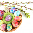 Beautiful Easter eggs in wicker basket isolated on white — Stock Photo