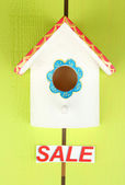 Decorative nesting box and sign on color background — Stock Photo