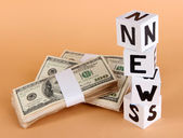 "White paper cubes labeled ""News"" with money on beige background — Stock Photo"