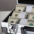 Suitcase with 100 dollar bills on grey background — Stock Photo #24430411