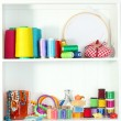 Beautiful white shelves with thread and material for handicrafts — Stock Photo #24432137