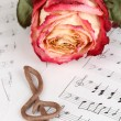 Royalty-Free Stock Photo: Treble clef and rose on musical background