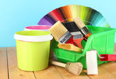 Paint pots, paintbrushes and coloured swatches on wooden table on blue background — Foto de Stock