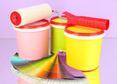 Set for painting: paint pots, paint-roller, palette of colors on lilac background — Stock Photo