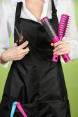 Peluquería en uniforme con herramientas de trabajo, sobre fondo de color — Foto de Stock