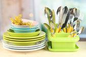 Desky, vidličky, nože, lžíce a další kuchyňské nádobí na světlé pozadí — Stock fotografie