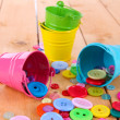 Colorful buttons strewn from buckets on wooden background — Stock Photo #24449541