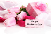 Bouquet of pink tulips and gift on cloth for Mother's Day, isolated on white — Stok fotoğraf