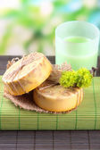 Hand made soap on grey bamboo mat, on green background — Stock Photo