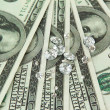 Beautiful shining crystals (diamonds) on money background - Stock Photo