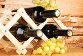 Bottiglie di vino inserito su supporto in legno sullo sfondo del muro in pietra — Foto Stock