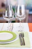 Table setting with glasses for different drinks on table on room background — Stock Photo