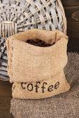 Ahşap zemin üzerine çuval içinde kahve çekirdekleri — Stok fotoğraf