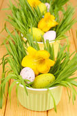 Easter eggs in bowls with grass on wooden table close up — Stock Photo