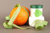 Orange with measuring tape and body cream, on color background — Stock Photo