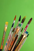 Many brush in paint on green background — Stock Photo