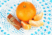 Tasty mandarine on color plate on blue background — Stock Photo