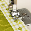 Closeup of sewing machine working part with green cloth — Stock Photo #24506853