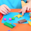 Child moulds from plasticine on table — Stock Photo #24506911