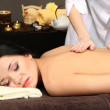Beautiful young woman in spa salon getting massage, on dark background — Stock Photo #24507049
