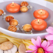 Beautiful candles swim in beautiful plate on yellow fabric close-up — Stockfoto