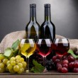 Bottles and glasses of wine and grapes on grey background — Stock Photo