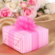 Beautiful gift on flowers background — Stockfoto