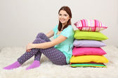 Beautiful young girl with pillows in room — Stock Photo