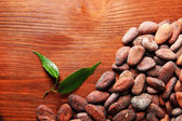 Cocoa beans with leaves on wooden background — Stock Photo