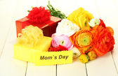 Ranunculus (persian buttercups) and gifts for mothers day, on white wooden background — Stock Photo