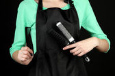 Hairdresser in uniform with working tools, isolated on black — Stock Photo