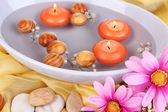 Beautiful candles swim in beautiful plate on yellow fabric close-up — Stock Photo