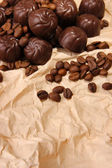 Chocolate candies and coffee beans, on beige paper background — Photo