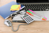 Laptop with stationery on table — Stock Photo