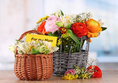 Many different flowers in baskets on room background — Stock Photo