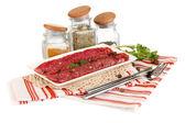 Tasty salami on plate on napkin isolated on white — Stock Photo