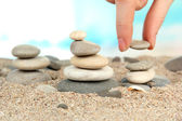 Hand builds tower of sea stones on sand on bright background — Stock Photo