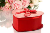 Beautiful gift on flowers background isolated on white — Stock Photo