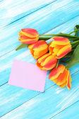 Beautiful orange tulips on color wooden background — Stock Photo