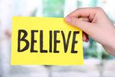 Believe word on piece paper in hand — Стоковое фото