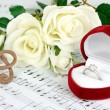 Treble clef, roses and box holding wedding ring on musical background — Stock Photo #24510675