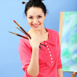 Beautiful young woman painter at work, on color background — Stock Photo