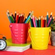 Colorful pencils in two pails with copybooks on table on orange background — Stock Photo #24515935