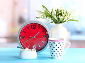 Cup tea and clock on bright background — Stock Photo