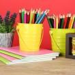 Colorful pencils in two pails with copybooks on table on red background — Stock Photo #24524135