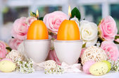 Easter candles with flowers on window background — Stock Photo