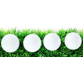 Golf balls on grass isolated on white — Stock Photo