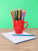 Colorful pencils in cup on table on green background — Stock Photo