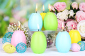 Easter candles with flowers on bright background — Stock Photo